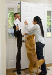 Dog and Woman holding back door