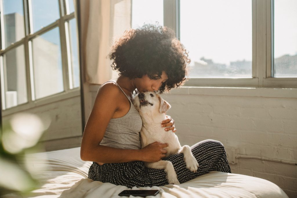 Young lady talks and bonds with her puppy to build connection and trust.