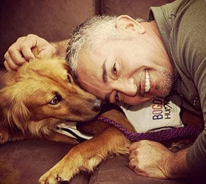 Caesar Millian lays and smiles with golden retriever puppy
