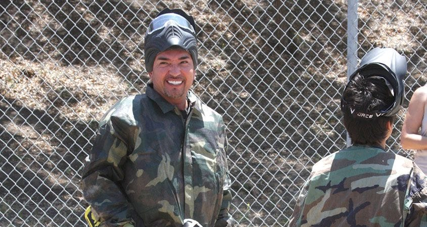 Cesar Millan playing paintball as a part of a pack