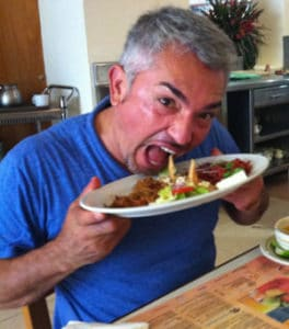 Ceesar Millan takes a big bite off of plate in restaurant